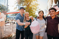 Friends eating cotton candy in amusement park Stock Photo