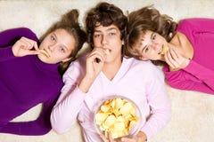 Friends eating crisps. Three teenage friends eating unhealthy crisps stock photos
