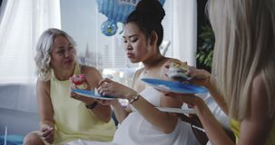 Friends eating dessert while celebrating young mother. Medium shot of friends eating dessert while celebrating young mother stock footage
