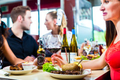 Friends eating and drinking in fast food diner. Friends or couples eating fast food and drinking beer and wine in a American fast food diner stock images