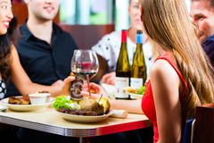 Friends eating and drinking in fast food diner. Friends or couples eating fast food and drinking beer and wine in a American fast food diner royalty free stock photography