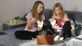 Friends eating fast food at home, watching a movie on a laptop. Pajama party two young women. Two young women eating fast food from a paper bag, use wooden stock footage