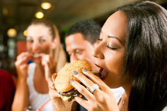 Friends eating fast food in a restaurant Royalty Free Stock Image
