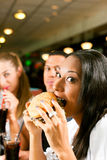 Friends eating fast food in a restaurant Royalty Free Stock Images