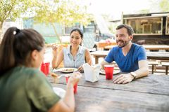 Friends eating from a food truck. Good looking Latin friends eating some oriental food from a food truck outdoors royalty free stock images