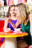 Friends eating ice cream in cafe Stock Photo