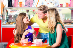 Friends eating ice-cream in cafe Royalty Free Stock Photo