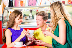 Friends eating ice-cream in cafe Royalty Free Stock Photos