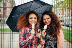 Friends eating ice cream in the rain Royalty Free Stock Photography