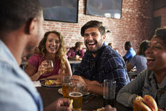 Friends Eating Out In Sports Bar With Screens In Background royalty free stock image
