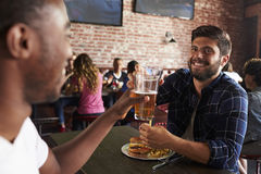 Friends Eating Out In Sports Bar With Screens In Background royalty free stock photos
