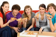 Friends Eating Pizza. Group Of Teenagers Sitting On A Couch Eating Pizza Royalty Free Stock Photos