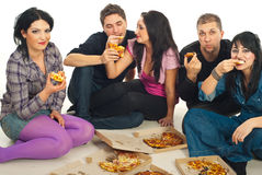 Friends eating pizza. Five friends sitting on  wooden floor and eating pizza Stock Photo