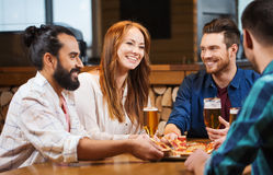 Friends eating pizza with beer at restaurant Stock Photography