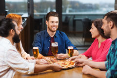 Friends eating pizza with beer at restaurant Royalty Free Stock Image
