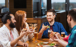 Friends eating pizza with beer at restaurant Stock Image