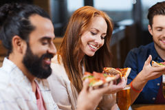 Friends eating pizza with beer at restaurant Royalty Free Stock Photos