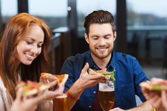 Friends eating pizza with beer at restaurant Stock Images