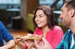 Friends eating pizza with beer at restaurant. Leisure, food and drinks, people and holidays concept - smiling friends eating pizza and drinking beer at Stock Photos