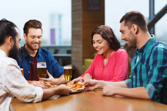 Friends eating pizza with beer at restaurant Stock Photo
