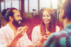 Friends eating pizza with beer at restaurant. Leisure, food and drinks, people and holidays concept - smiling friends eating pizza and drinking beer at Royalty Free Stock Image