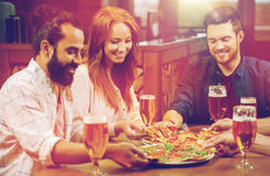 Friends eating pizza with beer at restaurant. Leisure, food and drinks, people and holidays concept - smiling friends eating pizza and drinking beer at Royalty Free Stock Images