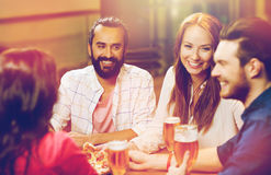 Friends eating pizza with beer at restaurant. Leisure, food and drinks, people and holidays concept - smiling friends eating pizza and drinking beer at Stock Photography
