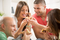 Friends eating pizza. Four friends enjoying to eating pizza together at home party Royalty Free Stock Photography