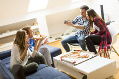 Friends eating pizza. Group of friends eating pizza and taking picture at home Stock Photography