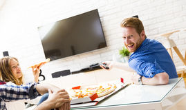 Friends eating pizza. Group of friends eating pizza together at home Royalty Free Stock Image