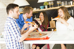 Friends eating pizza. Group of friends eating pizza together at home Royalty Free Stock Photo