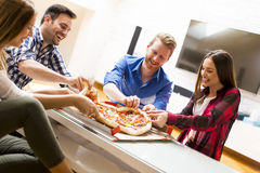 Friends eating pizza. Group of friends eating pizza together at home Royalty Free Stock Photos