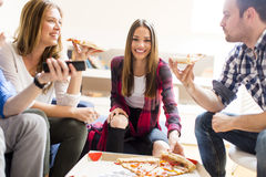 Friends eating pizza. Group of friends eating pizza together at home Stock Photo