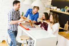 Friends eating pizza. Group of friends eating pizza together at home Stock Photos