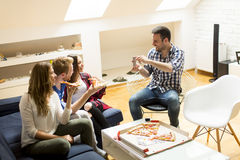 Friends eating pizza. Group of friends eating pizza together at home Stock Images