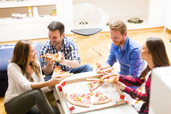Friends eating pizza. Group of friends eating pizza together at home Royalty Free Stock Photography