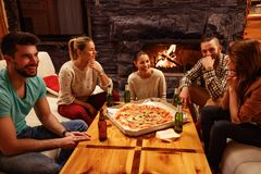 Friends eating pizza and having party. At home Stock Photography