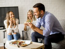 Friends eating pizza at home. View at friends eating pizza at home Stock Photography