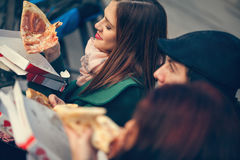 Friends Eating Pizza Outdoors. Group Of Young Friends Sitting On Bench And Eating Pizza royalty free stock images