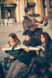 Friends Eating Pizza Outdoors. Group Of Young Friends Sitting On Bench And Eating Pizza Outdoors royalty free stock images