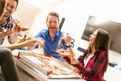 Friends eating pizza. In the room Stock Photo