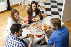 Friends eating pizza in th room Royalty Free Stock Photos