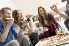 Friends eating pizza in th room Royalty Free Stock Photo