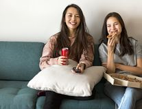 Friends eating pizza together on couch Royalty Free Stock Photo