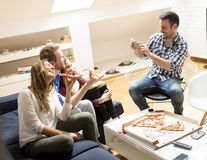 Friends eating pizza together at home Stock Image