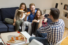 Friends eating pizza together at home Royalty Free Stock Photos