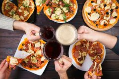 Friends eating pizza. Top view on male hands clinking mugs with. Beer over table with many pizzas. Party, friendship, pub, restaurant concept Stock Images
