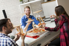Friends eating pizza. View at group of friends eating pizza together at home Royalty Free Stock Image