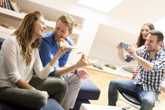 Friends eating pizza. View at group of friends eating pizza together at home Royalty Free Stock Photography