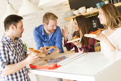 Friends eating pizza. View of the group of friends eating pizza together at home Stock Images